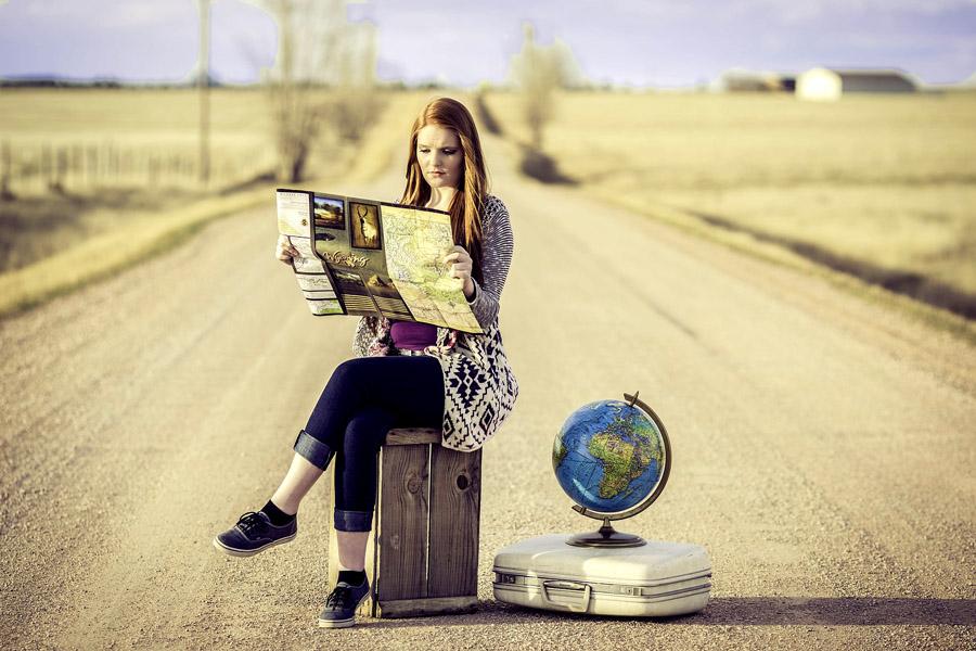Jeune femme lisant une carte au milieu d'une route déserte